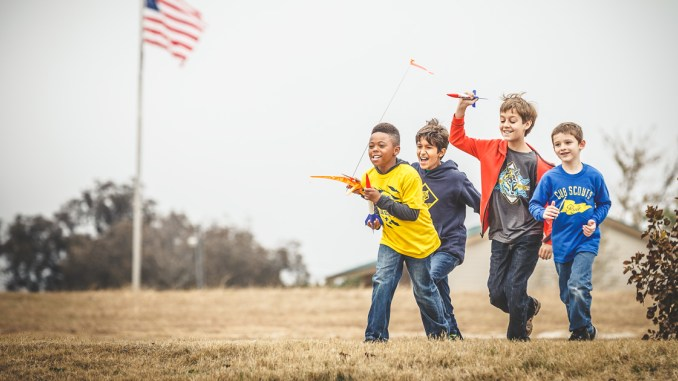 Cub Scouts running with rockets